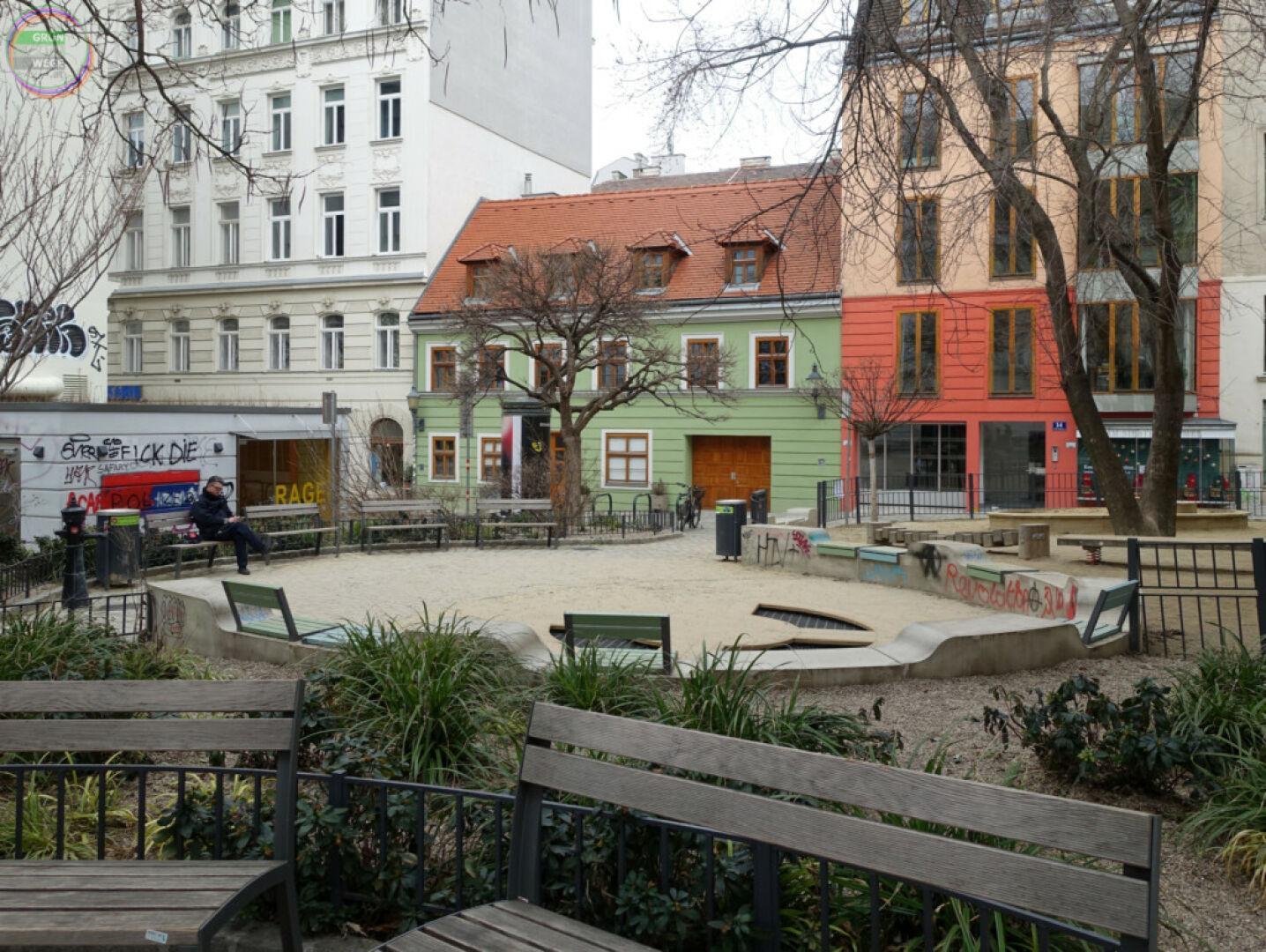 Bild Weg 5 Kleiner Park mit Sitzbänken in dicht verbautem Grätzl
