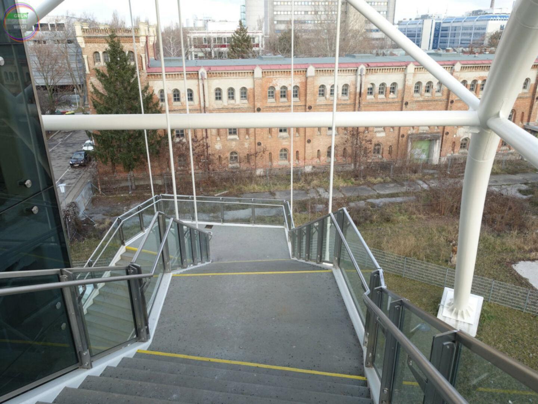 Bild Weg 5 Moderner Stiegenabgang von Steg vor altem Kasernengebäude